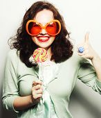 pic of tongue licking  - Young funny woman in big orange glasses licking lollipop with her tongue - JPG