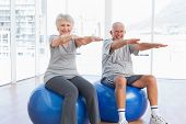 stock photo of casual wear  - Happy senior couple doing stretching exercises on fitness balls in the medical office - JPG
