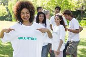Portrait of happy female volunteer pointing at tshirt with friends in background