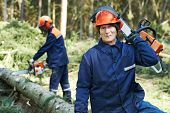 stock photo of man chainsaw  - Portrait of lumberjack logger worker in protective workwear with chainsaw at forest - JPG