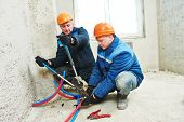 two repairman engineer installing house heating system at interior construction site