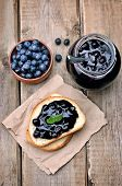 foto of jar jelly  - Toasted bread with blueberry jam and jam in glass jar on wooden table top view - JPG