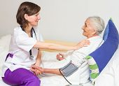 stock photo of nursing  - Happy joyful nurse caring for an elderly woman helping her days in nursing home - JPG