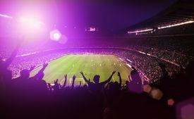 foto of hooligan  - crowded football or soccer stadium with purple light flare - JPG