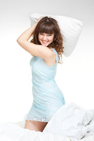 picture of pillow-fight  - lively young woman with pillow in the bed - JPG