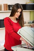 picture of secretary  - Pretty young secretary using a copy machine - JPG