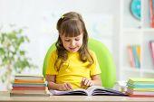 foto of nursery school child  - Happy child girl learning to read in nursery - JPG