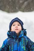 image of wonderful  - An cute young boy is outside looking up in wonder at the snow falling during the winter season - JPG