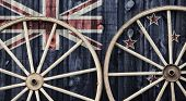 stock photo of wagon wheel  - A close up of two antique wagon wheels lying up against a building with wooden siding depicting the flag of New Zealand on its surface - JPG