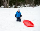 pic of toboggan  - A young boy dressed for cold weather poses with his red sled in the snow during the winter season - JPG