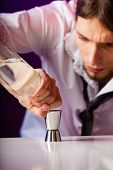 picture of bartender  - Young stylish man bartender preparing serving alcohol cocktail drink pouring vodka filling a jigger - JPG