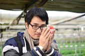 foto of overcoats  - Asian handsome tourist man wearing overcoat in strawberry greenhouse harvest fresh red - JPG