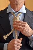 stock photo of hangman  - Hangman adjusting a noose rope like tie - JPG