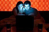 image of watching movie  - couple sitting on a couch in the evening and watching a movie on a laptop - JPG