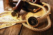picture of spyglass  - Marine still life spyglass and world map on wooden background - JPG