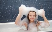 foto of suds  - smiling little girl sitting in a bath and imposes soap suds on her head - JPG
