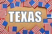 stock photo of texas flag  - Miniature flags of the United States of America form a border on brown card around the name of the state of Texas - JPG