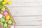 stock photo of egg whites  - Easter background with colorful eggs and yellow tulips over white wood - JPG