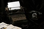 stock photo of short-story  - Old fashioned vintage photo of an old type writer with phone glasses and newspaper - JPG
