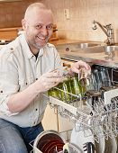 pic of dishwasher  - Homeworking smiling man filling up the dishwasher - JPG