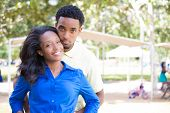 image of human soul  - Closeup portrait of a young couple guy in yellow shirt holding woman  from behind happy moments positive human emotions on isolated outdoors outside background - JPG
