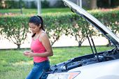 stock photo of hoods  - Closeup portrait young woman in pink tanktop having trouble with her broken car opening hood and texting for help on cell phone isolated green trees and shrubs outside background - JPG