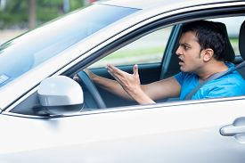 stock photo of pissed off  - Closeup portrait angry young sitting man pissed off by drivers in front of him and gesturing with hands - JPG