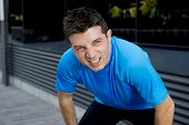 foto of breath taking  - young attractive man leaning exhausted after running session sweating taking a break to recover in urban street summer background - JPG