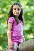 picture of straddling  - Cute little girl sitting outdoors against green leaves straddling a wooden pole and looking at the camera with a friendly smile - JPG