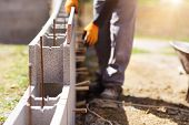 stock photo of bricklayer  - Bricklayer putting down another row of bricks in site  - JPG
