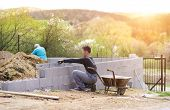 foto of bricklayer  - Bricklayer putting down another row of bricks in site - JPG