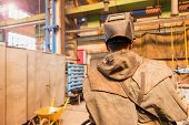 stock photo of protective eyewear  - Young man in a welding factory in protective workwear - JPG