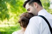 picture of fiance  - Young handsome man embracing and gently kissing his fiancee in summer green park - JPG