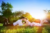 image of fiance  - Romantic couple in love kissing while lying on grass in spring park - JPG