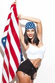 stock photo of independent woman  - Sexy woman holding usa flag in headscarf at white wall fourth of july independence day - JPG