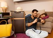 picture of leaving  - Loving couple reviewing photos taken on holiday before leaving apartment - JPG