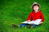 picture of 7-year-old  - Cute 7 years old boy sitting on a grass with a book - JPG