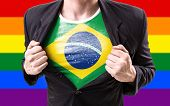 stock photo of south american flag  - Businessman stretching suit with Brazilian Flag with rainbow flag - JPG