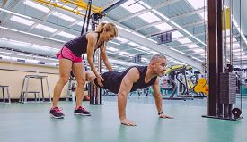 picture of suspension  - Female personal trainer teaching to man in a hard suspension training with fitness straps on a fitness center - JPG
