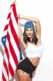 picture of independent woman  - Sexy woman holding usa flag in headscarf at white wall fourth of july independence day - JPG