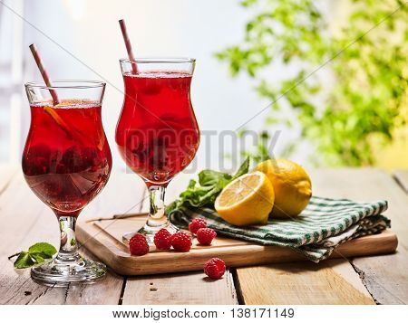 On wooden boards are ice cold cocktail two glasses with red berries lemon cocktail . Alcohol country
