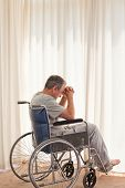 stock photo of amputation  - Thoughtful man in his wheelchair at home - JPG