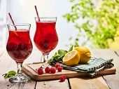 Постер, плакат: On wooden boards are ice cold cocktail two glasses with red berries lemon cocktail Alcohol country