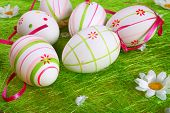 stock photo of easter-eggs  - Closeup of several Easter eggs over green grass - JPG