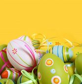 pic of easter card  - Pastel and colored Easter eggs on yellow background - JPG