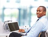 Portrait of a happy African American entrepreneur displaying computer laptop on white background