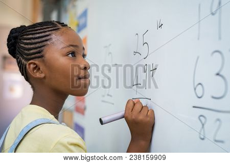 poster of Portrait of african girl writing solution of sums on white board at school. Black schoolgirl solving