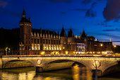 Night View Of Conciergerie Castle And Bridge Of Change (pont Au Change) Over River Seine. Castle Con poster
