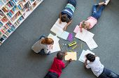 Elementary children lying on the floor and drawing at library. Top view of five multiethnic boys an poster
