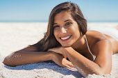 Happy young woman in swimwear lying on sand at beach. Portrait of smiling young woman relaxing on be poster